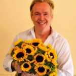 MIke Gaffney, flower designer, holding sunflowers